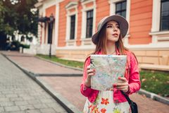 Young woman tourist searching for right way using map in Odessa, Ukraine. Girl lost in city. Traveler going sightseeing. Young woman tourist searching for right royalty free stock photo