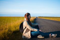 Young woman tourist sits on the road. Stock Image
