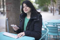 Young woman tourist sitting in a cafe outdoors, using smartphone, holding destination map stock photos