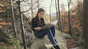 Young woman tourist sitting on the cliff in the woods looking at tourist card. Autumn is the season stock footage