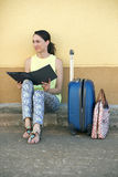 Young woman tourist sitting with luggage and a travel brochure i Stock Images
