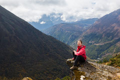 Young woman tourist sitting mountain edge rock. Nepal. Royalty Free Stock Image