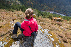 Young woman tourist sitting mountain edge rock. Nepal. Stock Photography