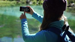 Young woman tourist is standing on a beautiful mountain lake and is enjoying scenic view in a sunny day. Traveler girl. Starts taking photos on smartphone 50 stock video footage