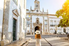 Woman traveling in Faro town on the south of Portugal. Young woman tourist standing on the city gate background in Faro town on the south of Portugal royalty free stock image