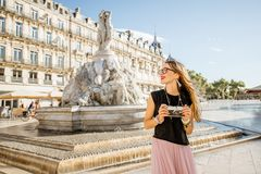 Woman traveling in Montpellier city, France. Young woman tourist standing with photo camera on the Comedy square with main fountain on the background in stock image