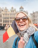 Woman tourist stands with the flag of Belgium on the background of the Grand-Place or the Grand Market Square in stock photos