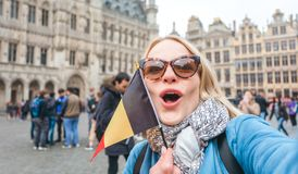 Woman tourist stands with the flag of Belgium on the background of the Grand-Place or the Grand Market Square in royalty free stock photo