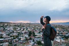 Young woman tourist stands on a sunset background over the city of Goreme in Turkey. Cappadocia. Tourism, rest, vacation Royalty Free Stock Images