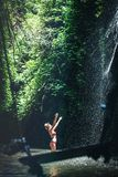 Young woman tourist with straw hat deep in the rainforest with waterfall background. Bali island. stock photos