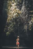 Young woman tourist with straw hat deep in the rainforest with waterfall background. Bali island. Indonesia stock photo