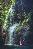 Young woman tourist with straw hat deep in the rainforest with waterfall background. Bali island. Indonesia stock images