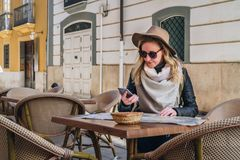 Young woman tourist in sunglasses and hat is sitting in street cafe at table, looking for a way on map, using smartphone Stock Photos