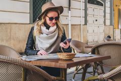 Young woman tourist in sunglasses and hat is sitting in street cafe at table, looking for a way on map, using smartphone Stock Image