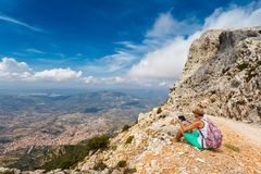 Young woman tourist with the tablet on background panoramic view from the mountains on the island of Sardinia in clear Royalty Free Stock Photos
