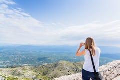 Young woman tourist taking photo of mountain landscape Stock Photo