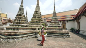 Young woman tourist taking pictures with smartphone at temple sightseeing in Bagnkok Thailand during traveling stock video