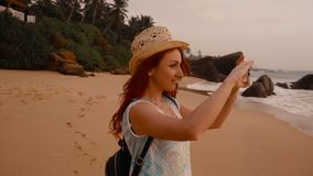 Young woman tourist taking pictures of the sunset by the ocean. Young red-haired woman tourist taking pictures using a smartphone sunset on the ocean beach, slow stock footage