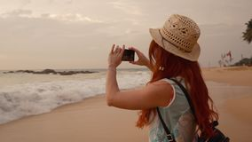Young woman tourist taking pictures of the sunset by the ocean. Young red-haired woman tourist taking pictures using a smartphone sunset on the ocean beach, slow stock video footage
