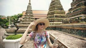 Young woman tourist taking selfie with smartphone at temple sightseeing in Bagnkok Thailand during traveling stock video