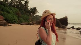 Young woman tourist talking on the phone at the ocean beach. Young red-haired female tourist talking on the phone at the ocean beach at sunset stock video
