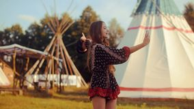 Young woman tourist talking on the phone and smiling on the background teepee / tipi- native indian house. Traveler chatting, blog stock footage