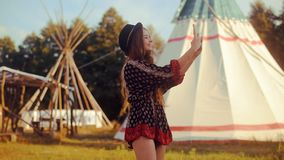 Young woman tourist talking on the phone and smiling on the background teepee / tipi- native indian house. Traveler chatting, blog stock video
