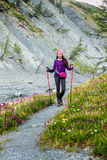 Young woman tourist walking alpine trail Stock Photos