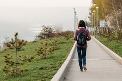 Young woman tourist walking on road in Park. rear view royalty free stock photography