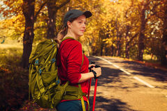 Young woman tourist. Walking with sticks and backpack on road at autumn season Royalty Free Stock Image