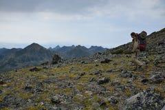 Young woman tourist walking on top of the mountain ridge Barguzi Stock Photo