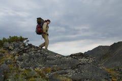 Young woman tourist walking on top of the mountain ridge Barguzi Stock Images