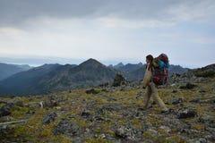 Young woman tourist walking on top of the mountain ridge Barguzi Royalty Free Stock Photos