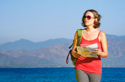 Young woman tourist walks on the seashore  reading the map. Royalty Free Stock Photos