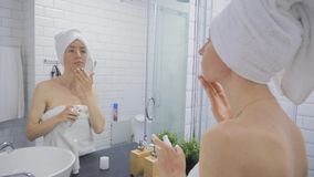 Young woman in towel applying cream to face and looking to mirror at home bathroom. Beauty, lifestyle, skin care concept.  stock video