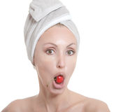 Young woman in towel, with a cherry berry Stock Photography
