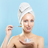 Young woman in towel with a cosmetic cream Stock Images