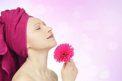 Young woman with towel and gerbera flower Royalty Free Stock Image
