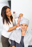 Young woman with towel on head in hair salon. Royalty Free Stock Photo