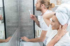 Young woman with towel on head looking at mirror while husband brushing teeth behind stock photos