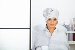 Young woman with towel on head sitting in hair salon. Royalty Free Stock Photography