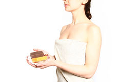 Young woman with a towel holding soap isolated on white backgrou Stock Image