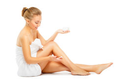 Young woman in towel terry puts cream on legs stock photography