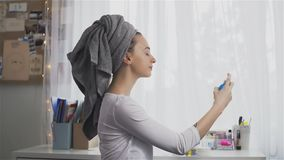 Young woman in towel using hair spray