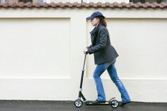 Young woman with toy scooter Royalty Free Stock Photography