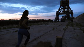 A young woman in a tracksuit jogging along the sand pier of the cargo port, in the twilight of the morning dawn. View stock video