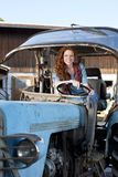 Young woman on a tractor Royalty Free Stock Image