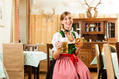 Young woman in traditional Bavarian Tracht in restaurant or pub Stock Images