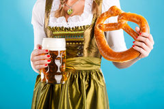 Young woman in traditional clothes or dirndl. Young woman in traditional Bavarian clothes - dirndl or tracht with a beer stein and beer and pretzel stock photography