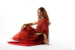 Young woman in traditional dress sit on white Royalty Free Stock Photo